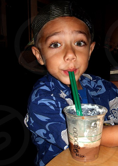 Little boy is wide-eyed with a 'brain freeze' as he sips chocolate milk. photo