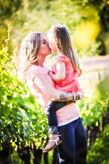 person kissing her child photo
