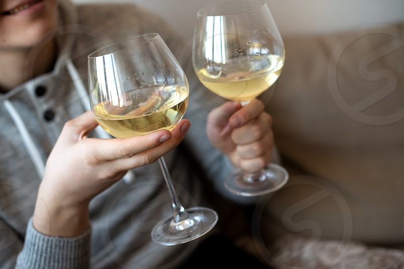 young man hands holding white wine glasses photo