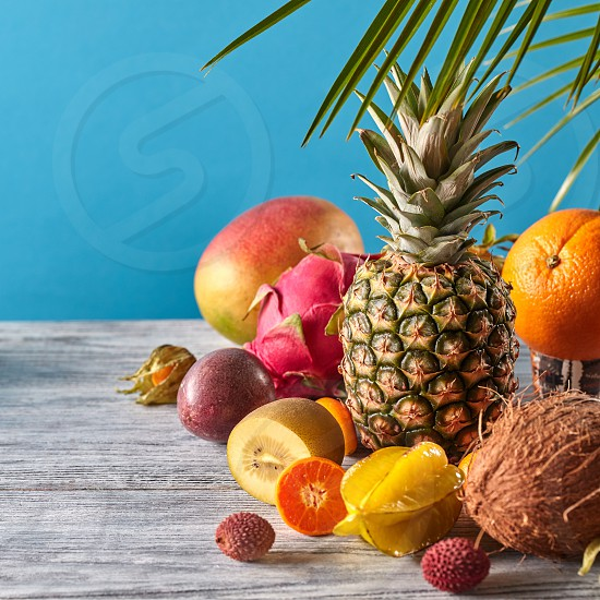 Group of exotic tropical fruits. Mango dragon fruit passion fruit coconut pineapple carambola kumquat on a blue background with copy space. Vegetarian healthy concept. photo
