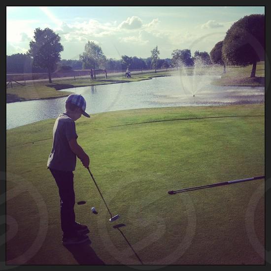 Boy golfing on putting green photo