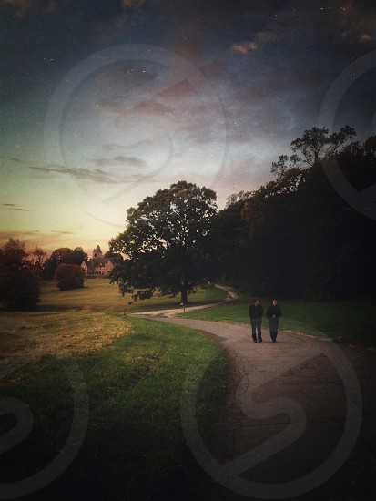 a storybook-like scene: couple walking down a winding path at dusk photo