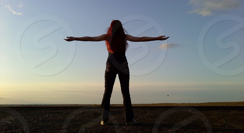 Redhead woman with her arms outstretched to the open sky at sunset.  photo