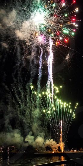 Multiple fireworks burst over lake photo