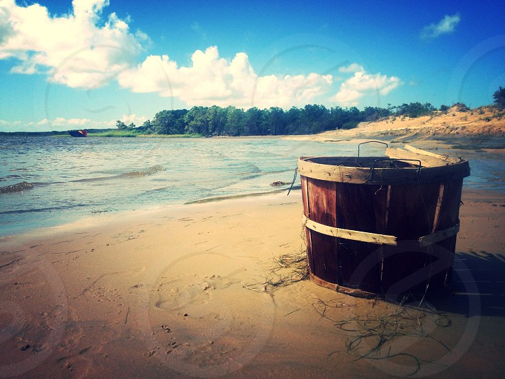 brown wooden bucket on white sand near to body of water photo