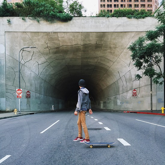 man riding a skateboard standing in the middle of the road in front of a tunnel photo