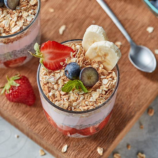 Healthy breakfast with homemde granola yogurt slices of strawberries banana blueberries oat flaks chia seeds on a wooden board. Concept of healthy dieting food. photo