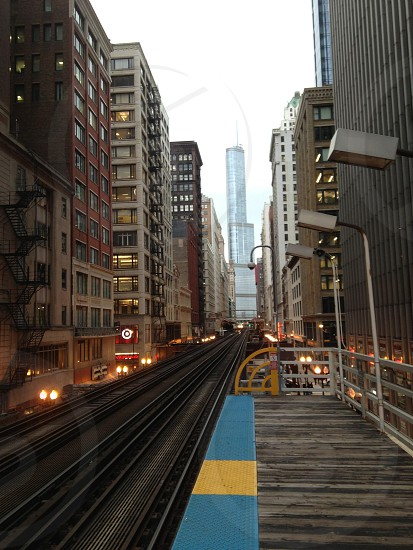empty railroad track in between of buildings during day photo