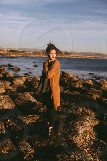 woman in brown jacket and black leggings standing in rocky beach photo