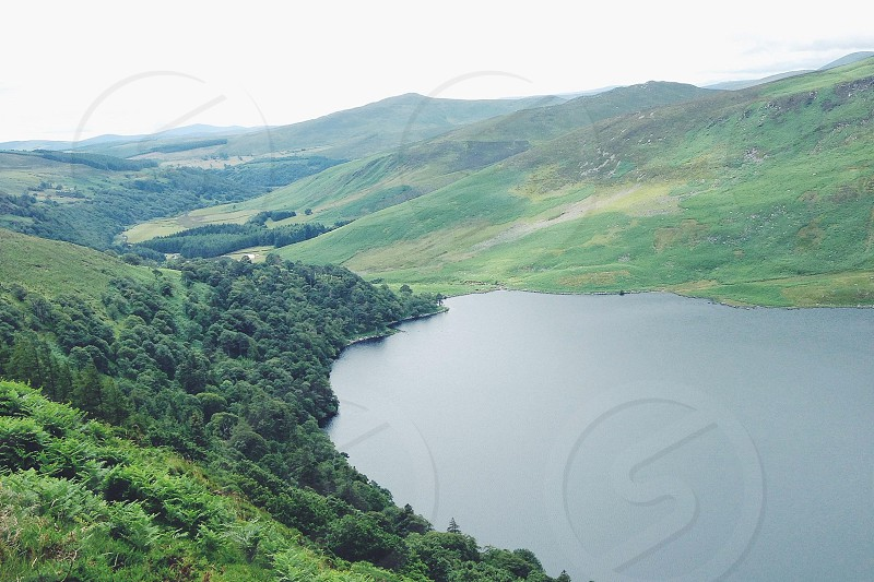 calm water in the middle of green hills photo
