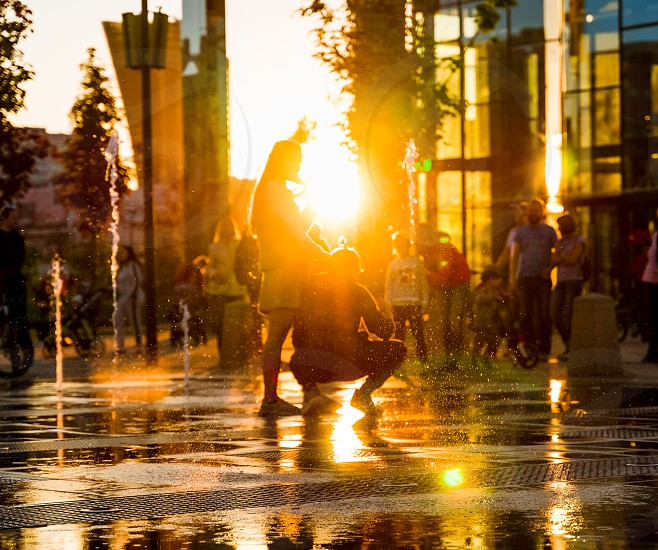 City fountain people backlit by setting sun photo