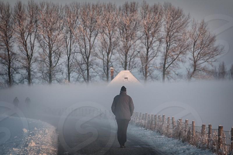 man walking on black asphalt road photo