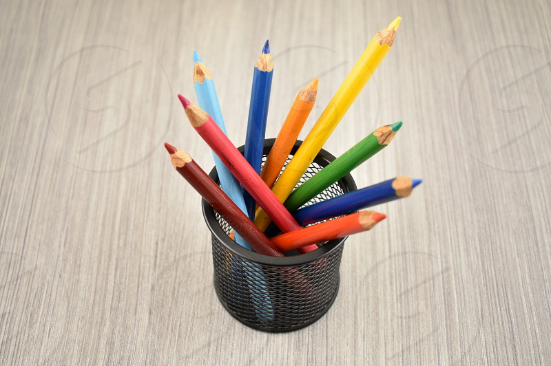 Color pencils. Colored pencils in cup. Crayons on a wooden background. Set of colored pencils. Art supplies images. School supplies for drawing photo