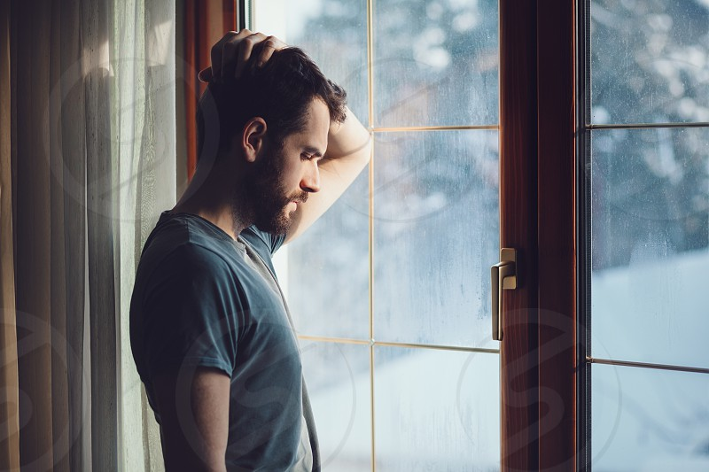 Young sad mad sitting by the window in regret photo