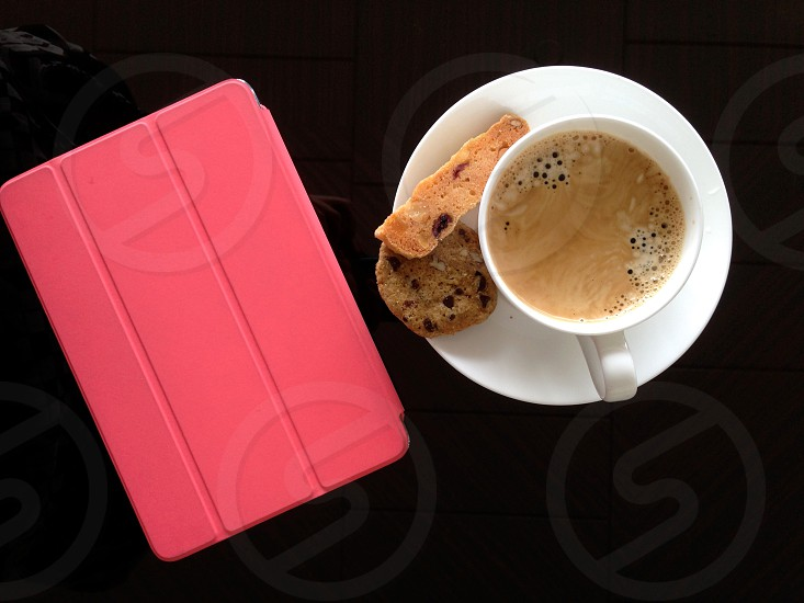 pink smart case beside white ceramic cup and saucer photo