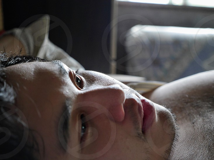 Closeup face man lying thinking deep pensive sad gloomy photo