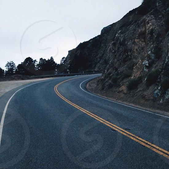 gray concrete road and rocky mountain photo