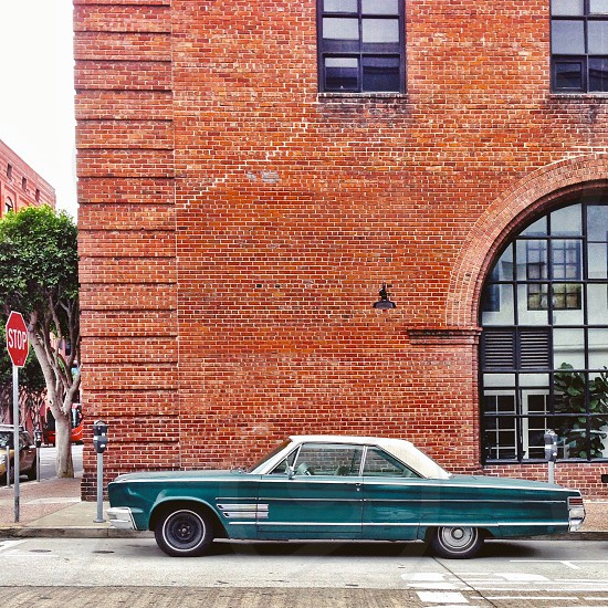 Vintage car in front of brick building photo