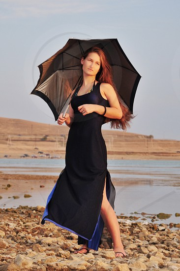 woman in black tank dress standing while using grey black umbrella brown stony field by the field photo