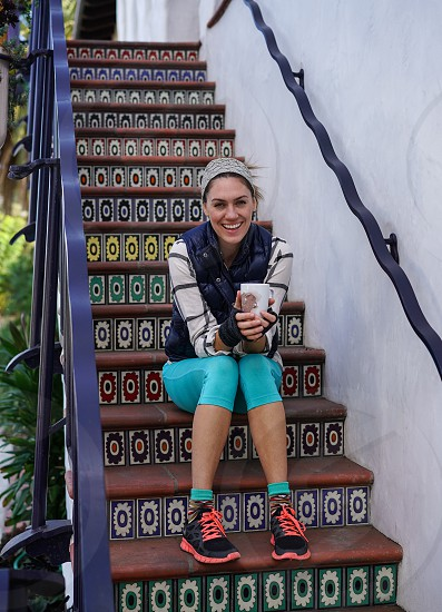 smiling woman in black bubble vest and teal leggings sitting on brown stairs during daytime photo