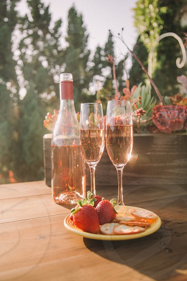 two champagne flutes filled with rose wine on a table next to the bottle and a plate strawberries and crackers photo