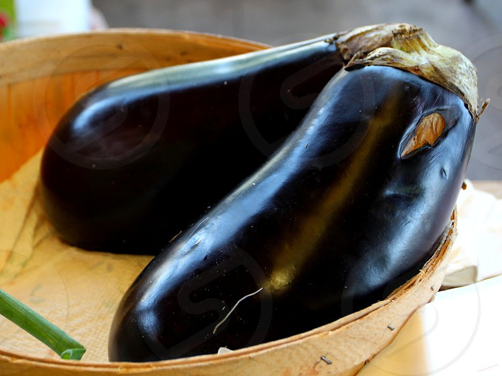 Eggplant in wooden basket at farmers market photo