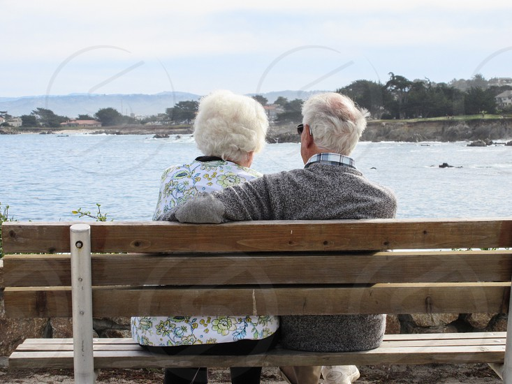 Elderly couple sitting on a bench watching the ocean eternal love long marriage love in old age romance  photo