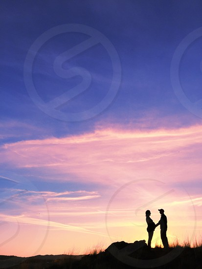 silhouette of man and woman holding hands on hilltop under pink sky during sunset photo