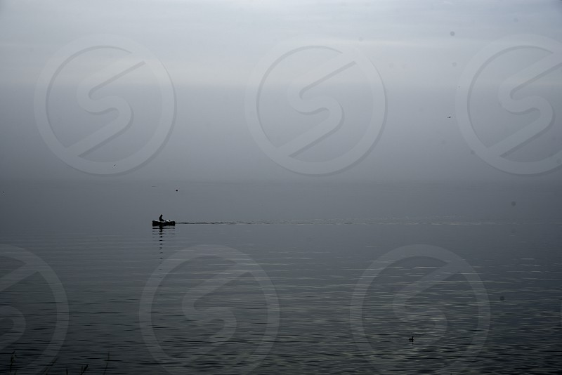 Foggy row man boat silhouette misty sea water world photo
