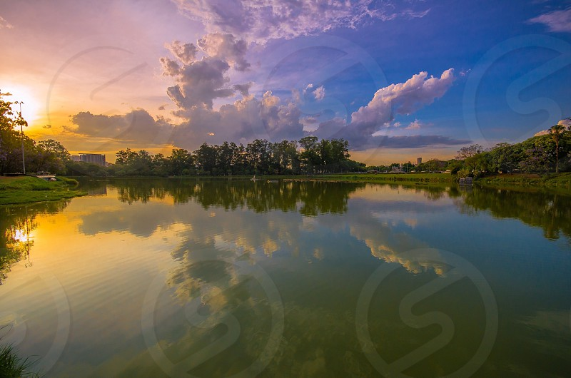 clouds reflected in tree lined lake photo