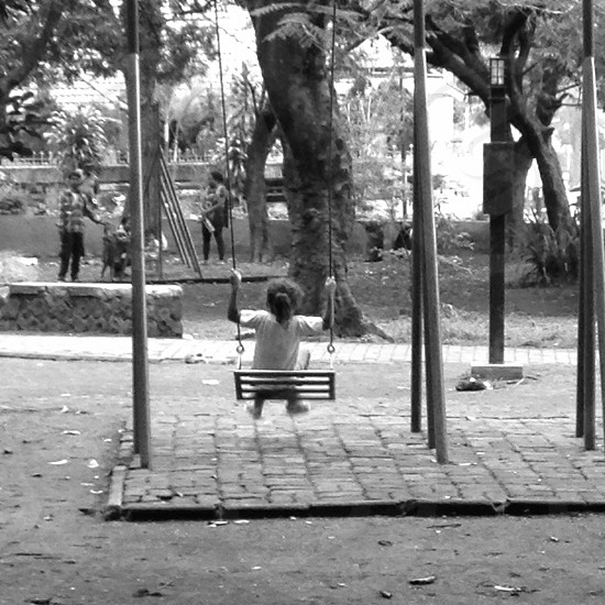 grayscale photo of girl on swing photo