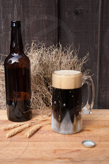 frosty mug of coffee stout with beer bottle photo