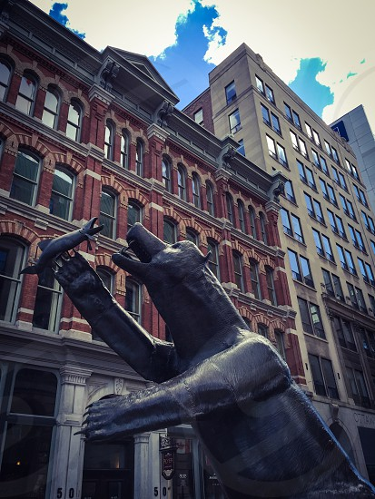 Outdoor day vertical portrait Ottawa Ontario Canada city urban architecture building brick red red brick sculpture statue carving bear iron fish hunt photo