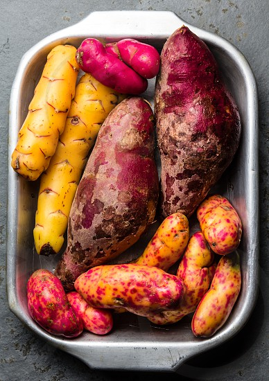 Peruvian raw ingredients for cooking - yuca colored sweet potatoes and camote batata. Top view. photo