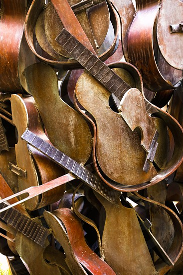 Broken and stacked acoustic guitars create an artistic background photo