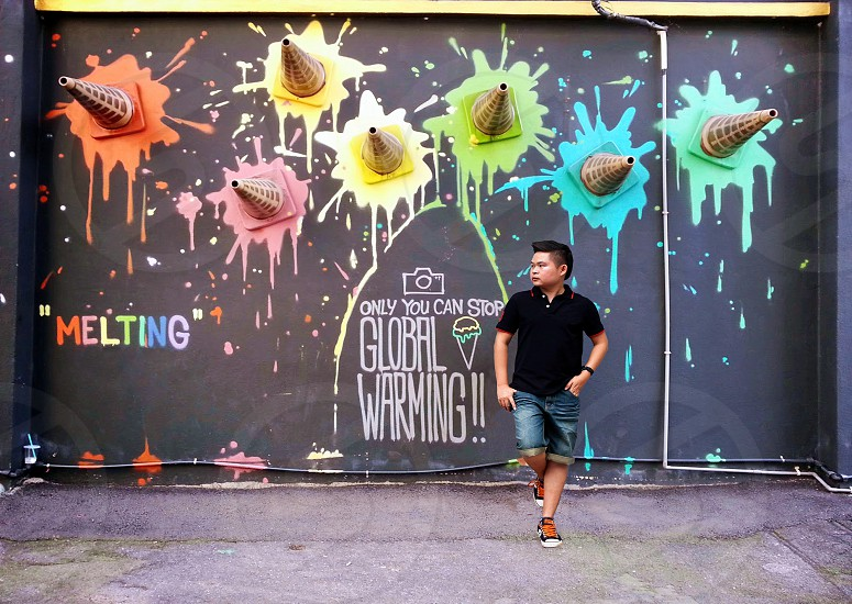 man in black polo shirt posing in front of graffiti painted wall photo