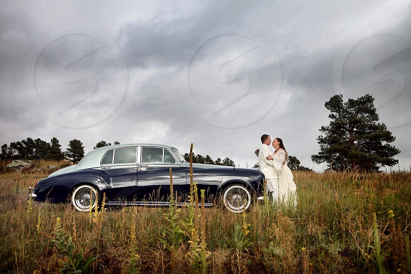 Newlyweds on a classic Rolls Royce.  Nature tree clouds gloomy storm happy celebration wedding marriage bride groom blue two-tone spokes white wall bouquet love together embrace. photo