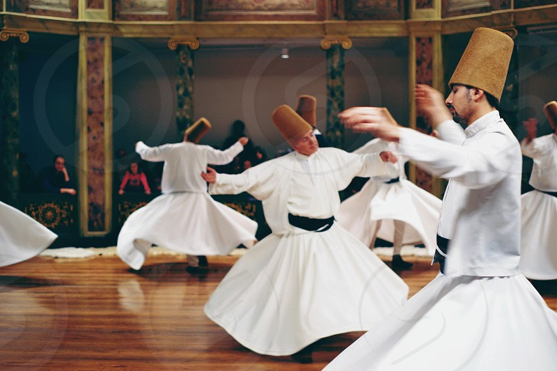 people in white dress dancing on the floor with brown headdress photo