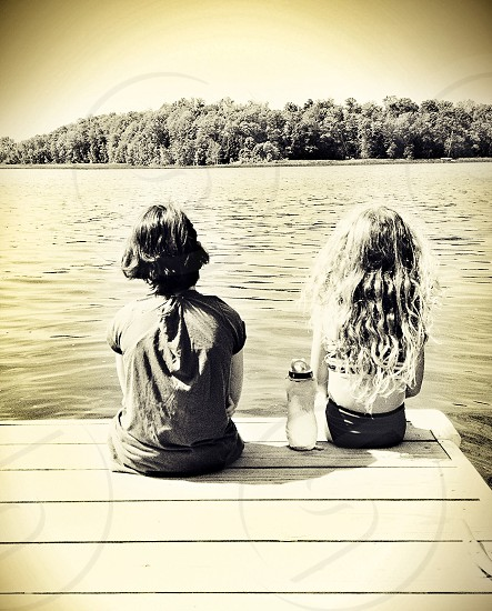 2 girl's sitting on dock black and white photograph photo