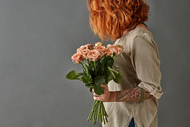 Young red-haired girl with a tattoo holds a bouquet of pink roses on a gray background photo