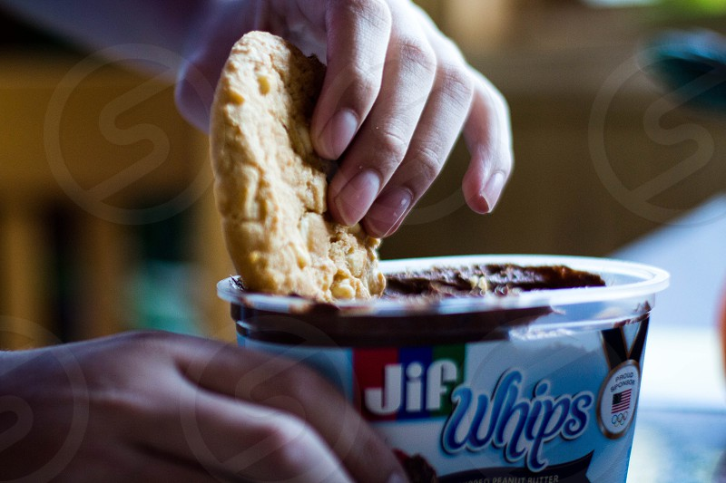 photography of person holding oatmeal cookie dipping on Jif Whips container photo