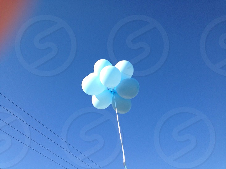 white white balloons flying on the sky photo