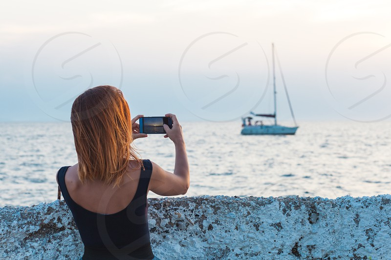 Young woman tourist taking photo with smartphone by the sea photo