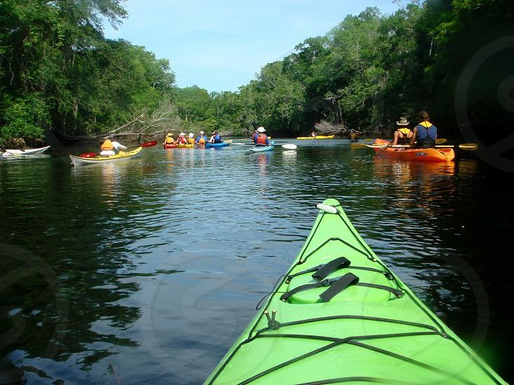 pov kayaking in Florida in green kayak among many multicolored kayaks photo