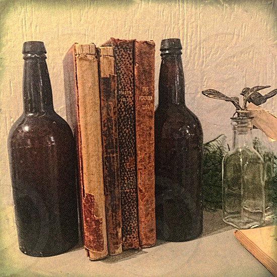 two vintage brown beer bottles are used as bookend for vintage books photo