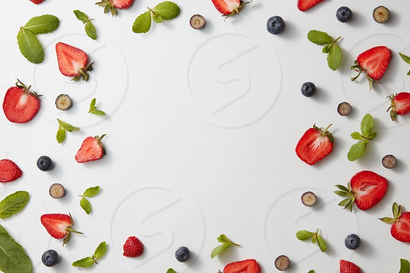 Green mint leaves blueberries halves of strawberries on a gray background with copy space. Food Frame. Flat lay photo