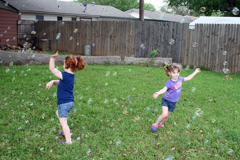 Two young sisters running and chasing bubbles in a yard. photo