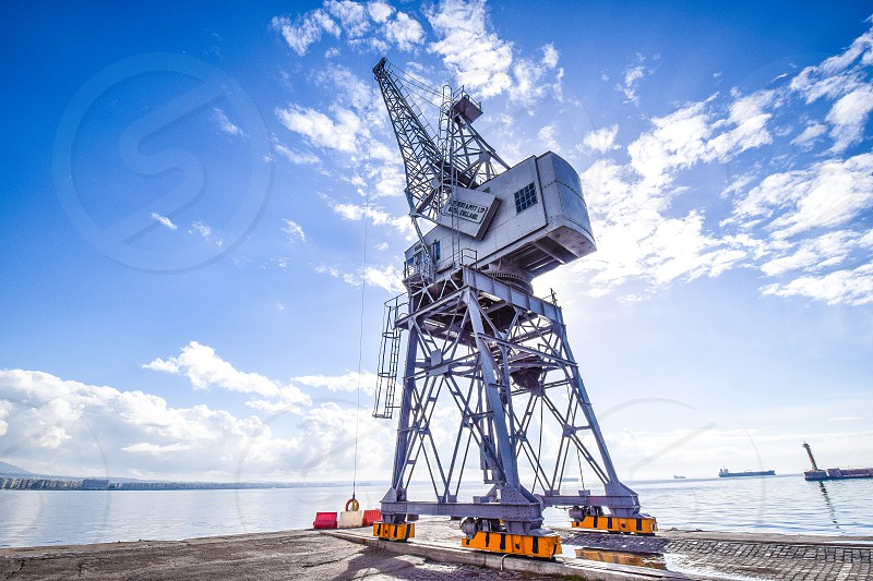 low angle photography of gray cargo machine under blue white cloudy sky photo