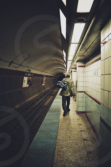 man wearing brown jacket holding grey duffel bag walking on train station beside underground train tracks photo