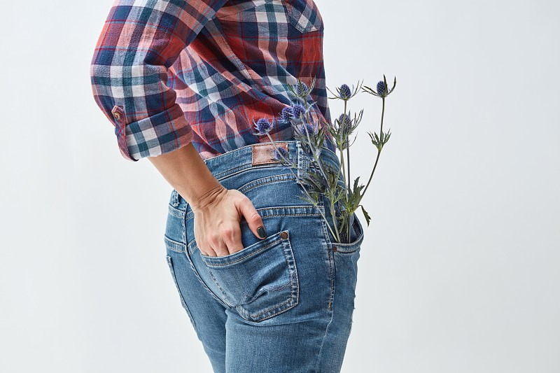 A woman in jeans standing with her back with an eryngium flower in her pocket. Holiday. Mother's Day photo